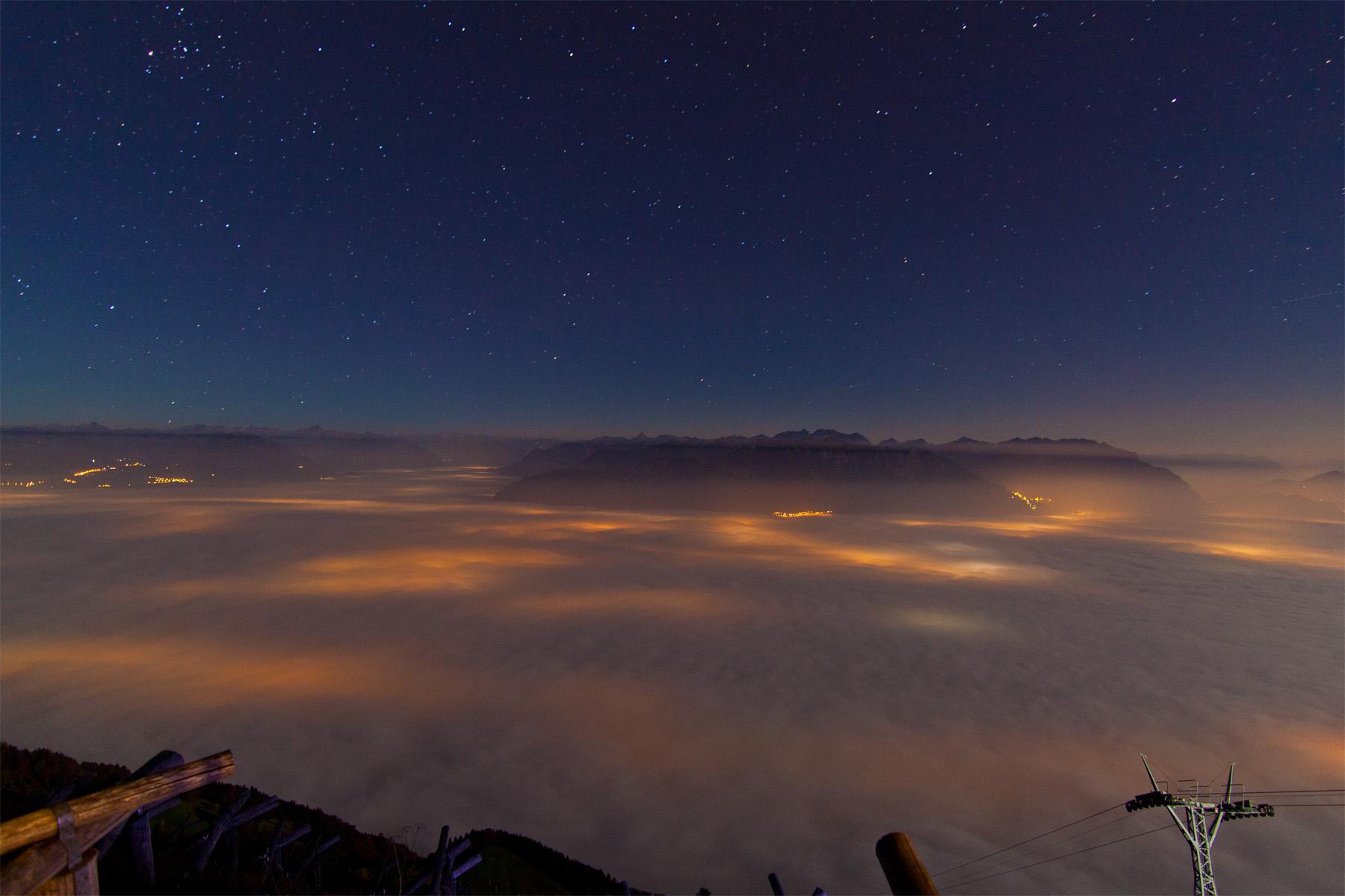 Blick von Staubern auf das Nebelmeer des Rheintals und des Walgaus; orange Flecken sind Lichtkegel der Ortschaften unterhalb des Nebels; Vordergrund Liftstütze der Seilbahn; Hintergrund Drei Schwestern