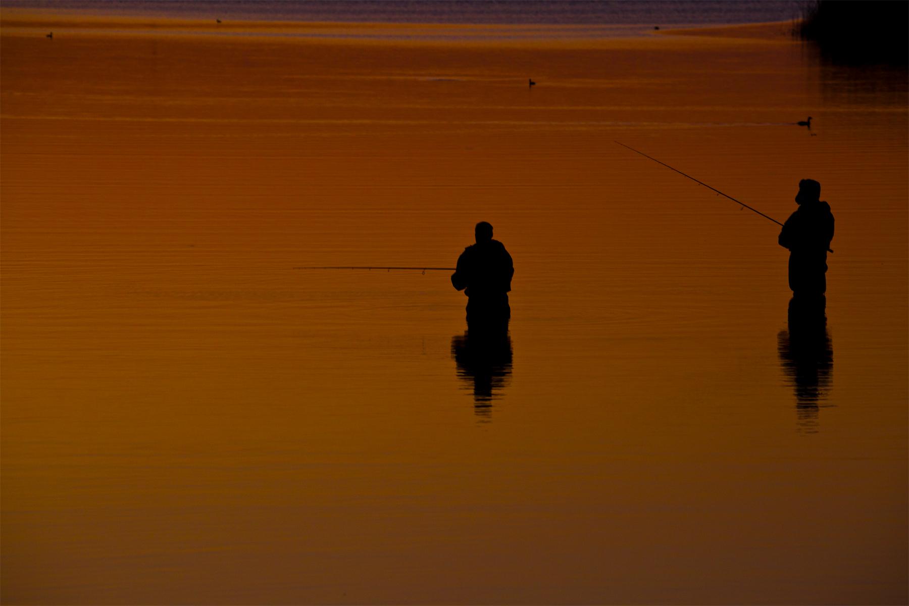 Fischer im Orange stehend